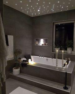 Une salle de bain dans les tons marrons avec une grande baignoire