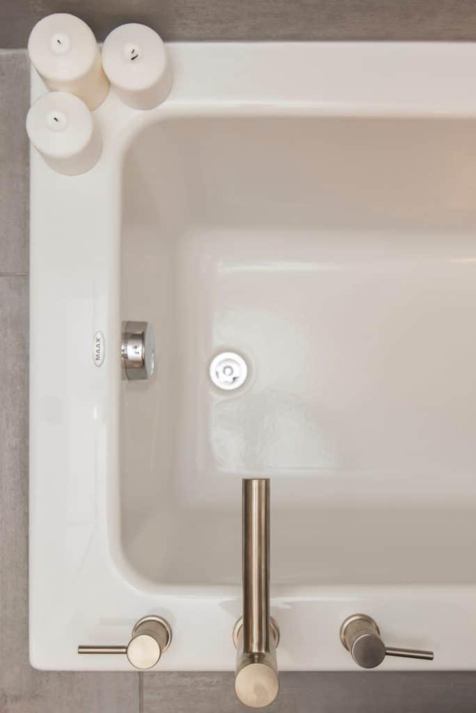 Une baignoire blanche avec un robinet argenté