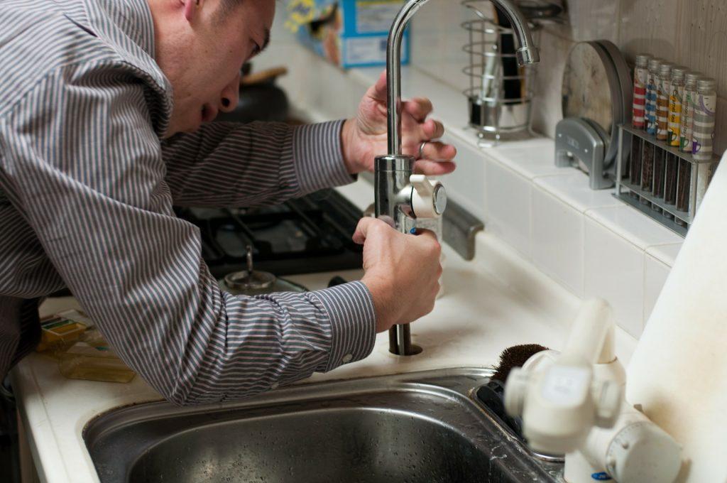 Un homme en train de réparer le robinet d'un évier