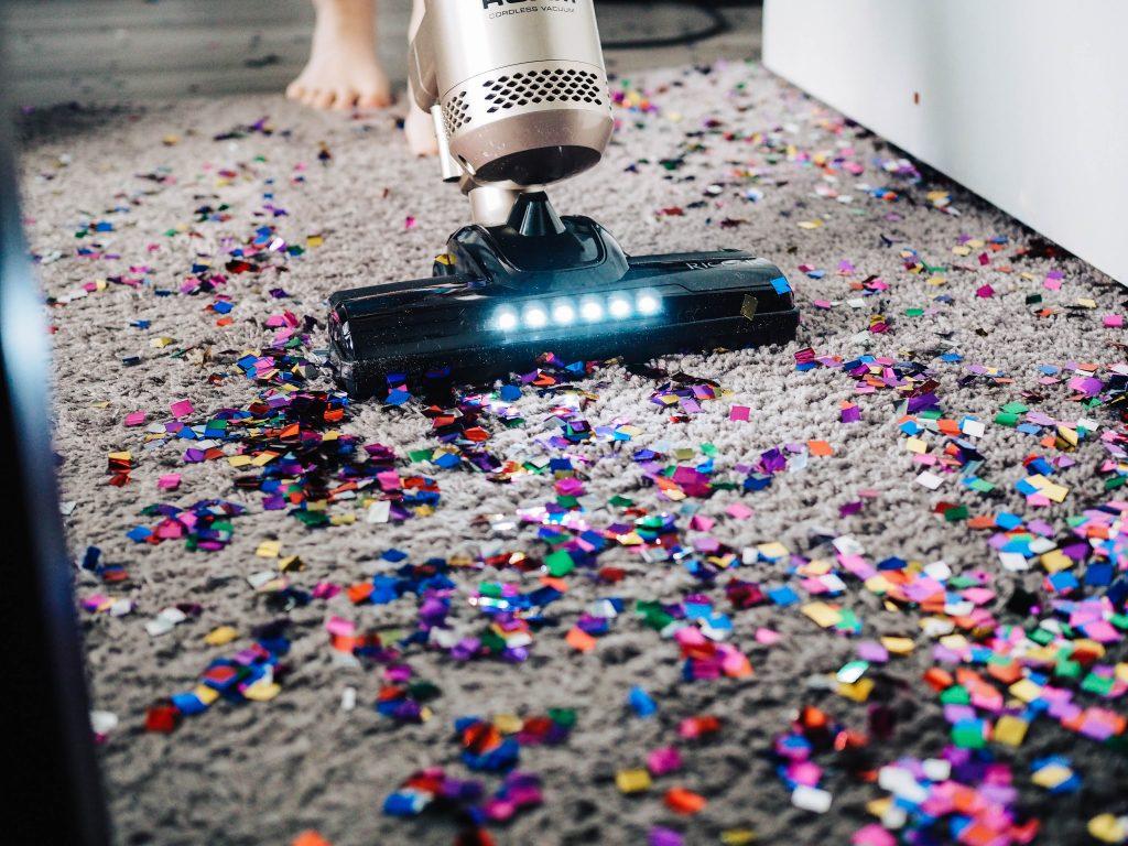 Un aspirateur qui nettoie un tapis recouvert de confettis